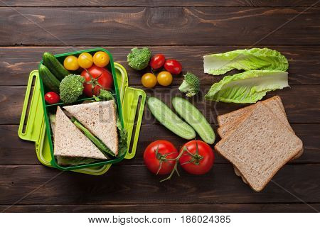 Lunch box with vegetables and sandwich on wooden table. Kids take away food box. Top view