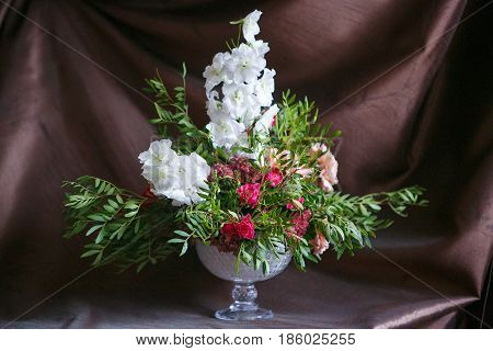 High bouquet in a shiny vase of delphinium, roses and carnations in a shiny vase