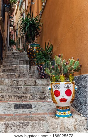 Brightly colored face flower pot with fruiting prickly pear cactus standing on a steep narrow flight of stone steps in Taormina, Sicily, Italy
