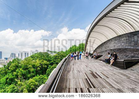 Singapore - February 19 2017: Tourists walking on the Henderson Waves. Amazing pedestrian wooden bridge curving and leading to a green park. Beautiful cityscape.