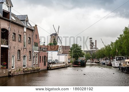 Gouda Netherlands - August 4 2016: Canal of Gouda with vessels and windmill a cloudy day. Gouda is famous for its cheese and its 15th-century city hall.