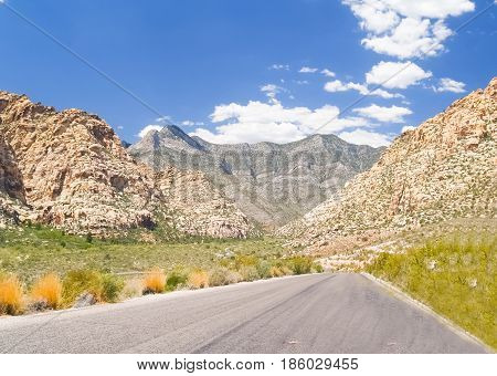 Road heading into canon between surroung hills in desert of Red Rock Canyon Nevada.