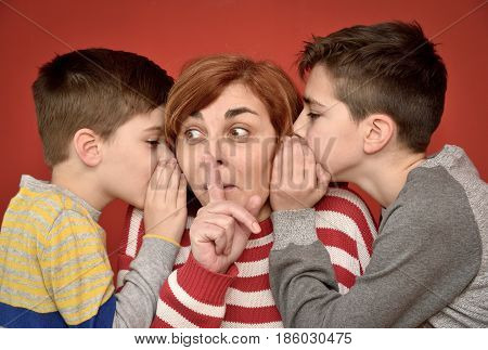 Sons whispering secret into ears of surprised mother with index finger on her mouth