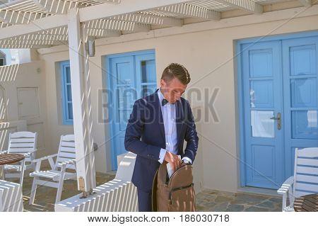 SANTORINI, GREECE - AUGUST 05, 2015: handsome bridegroom fill back pack on Santorini