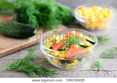 Cucumbers, tomatoes and corn salad. Bright, colourful and yummy salad in a bowl and on wooden table. Healthy diet vegetable salad photo. Rustic stile