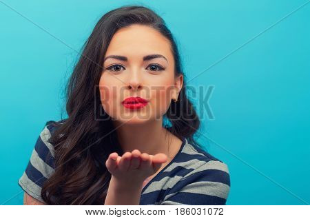 Portrait Of The Beautiful Smiling Girl Which Sends An Air Kiss  On The Blue Background.