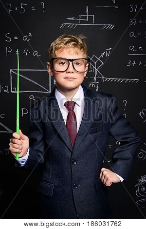 Smart schoolboy in black suit and glasses standing by a school blackboard. Educational concept.