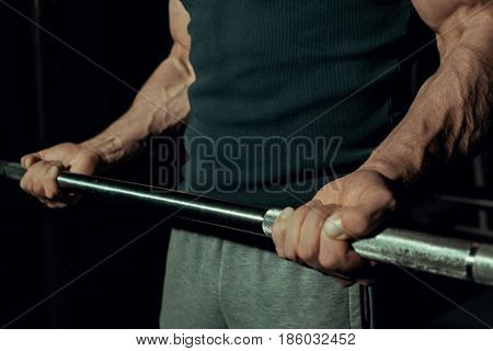 Inflated hands of a young guy close-up. Biceps on a black background