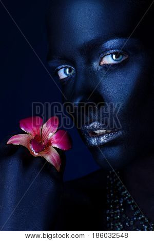 Beauty portrait. Close-up portrait of a beautiful young woman with perfect black skin posing with orchid brooch. Body painting project. Cosmetics and make-up. Jewellery.