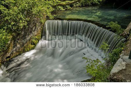 Semicircular dam on river that cause waterfall