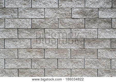 closeup of old grey brick facade with black lines