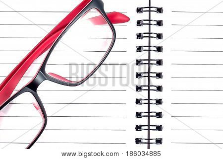 Opened notepad with glasses white education concept background