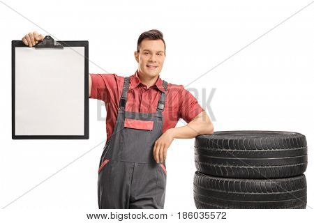 Mechanic leaning on a pile of tires and holding a blank clipboard isolated on white background
