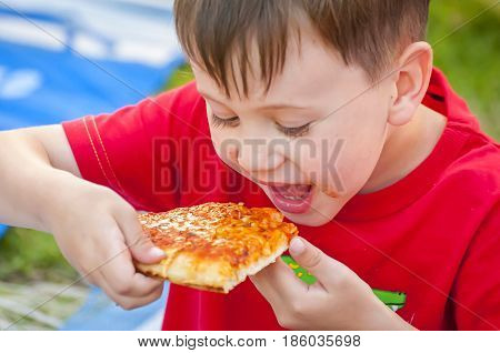 Cute little Caucasian hungry kid eating pizza at a pizza party.