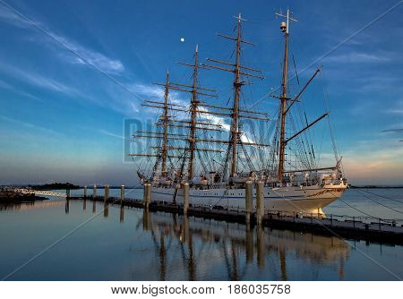 Japanese four masted sailing ship  in sunset-time against the background of bright blue sky and white cloud.
