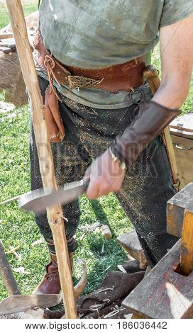 Craftsman with traditional medieval clothes manufactures a wooden arch with ancient method. Close up. Shallow deep of field.
