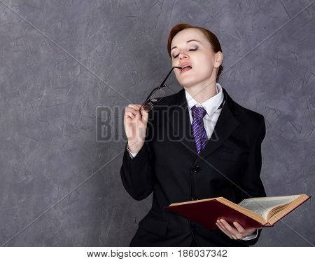 Female lawyer holding a big book with serious expression, woman in a man's suit, tie and glasses.
