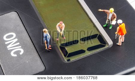 fixing the problem concept closeup of miniature figurine of workers reparing zero number on a big black calculator