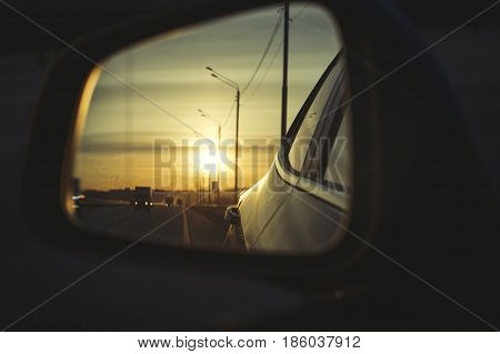 Sunrise on highway road in left side view mirror driver. Focus on reflection in smaller mirror. Close up photo of left side view mirror.