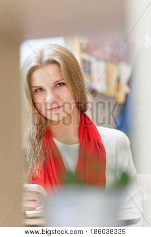 One european young attractive woman with red scarf is reading book and write some thing in notebook by pen on the table inside light cafe at day time.