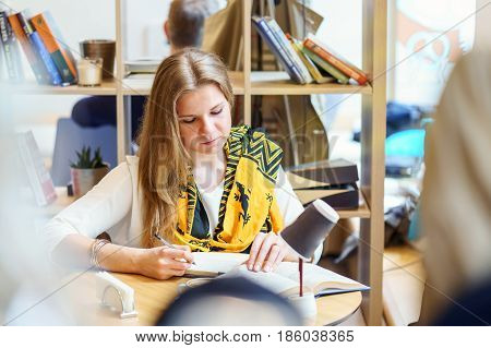 One european young attractive woman with yelow scarf is reading book and write some thing in notebook by pen on the table inside light cafe at day time.