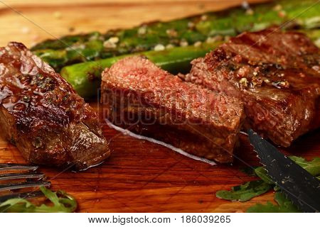 Cut Slices Of Grilled Beefsteak On Board Close Up
