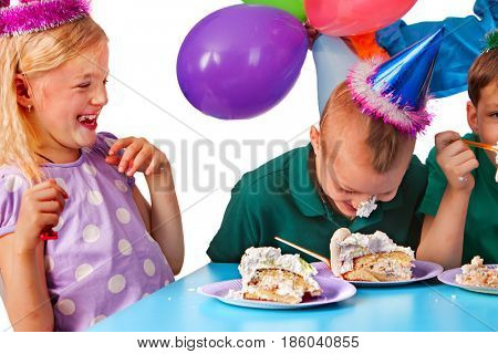 Birthday children celebrate party and eating cake on plate together . Portrait of three kids with messy face happy girl and boy in party hat sitting for table. Boy got stained with birthday cake.