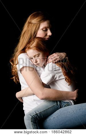 Mother And Little Daughter Hugging Each Other Isolated On Black