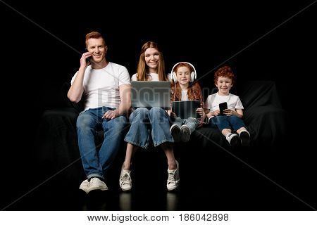 Family Using Various Digital Devices Isolated On Black