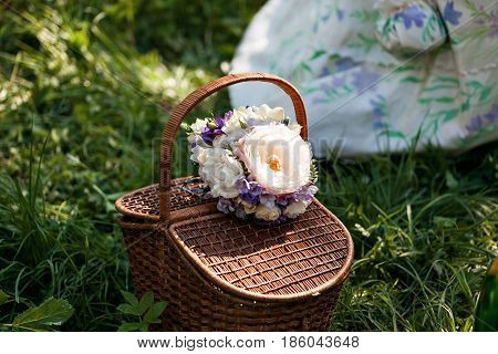 Romance, love, valentine's day concept - wicker basket with bouquet of flowers, bottle wine on the grass. Spring fresh sunny background.