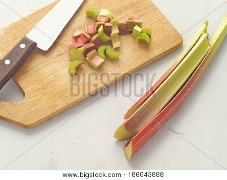Cooking process. Preparing rhubarb cake. Rhubarb stems arranged on old wooden background, whole and cut on pieces. Top view.