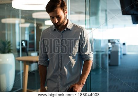 Uphappy businessman looking down against glass at office