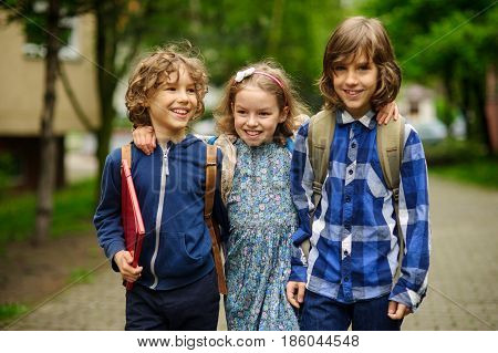 Three little school students two boys and the girl stand in an embrace on the schoolyard. Children's friendship.