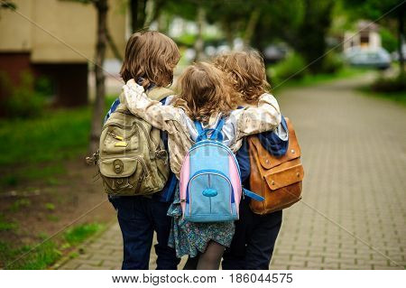 Three little school students go in an embrace to school. Children's friendship.