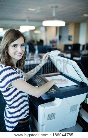 Portrait of smiling businesswoman using copy machine in office