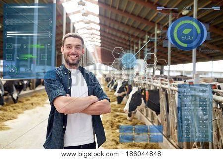 agriculture industry, people and animal husbandry concept - happy smiling young man or farmer with herd of cows in cowshed on dairy farm