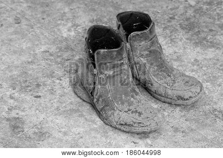 Pair of very dirty boots - black and white picture.