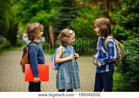 Little school students briskly talk on the schoolyard. Children have a good mood. Warm spring morning. Behind shoulders at schoolmates schoolbags.