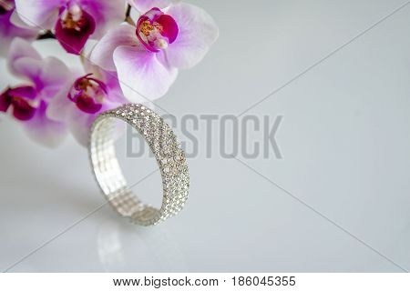 Zirconium bracelet lies on the background of purple orchids