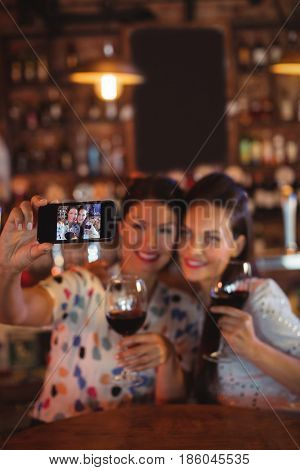 Young women taking a selfie from mobile phone while having a red wine in pub