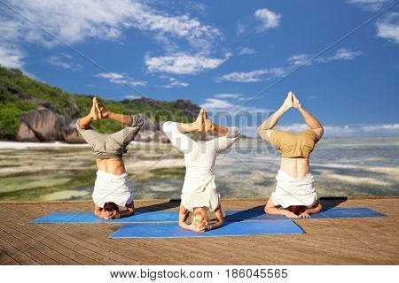 fitness, yoga and sport concept - people making headstand pose over exotic tropical beach background