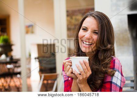 Beautiful laughing woman drinking coffee
