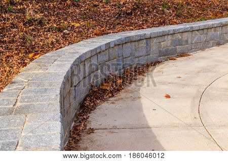 The tone fence on the side of concrete footpath and dry leaves in sunny autumn day