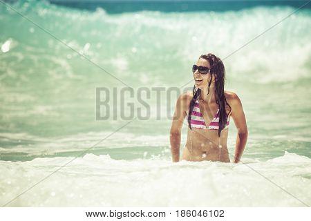 Beautiful bikini woman swimming at beach