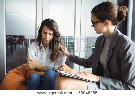 Counselor consoling unhappy woman during therapy