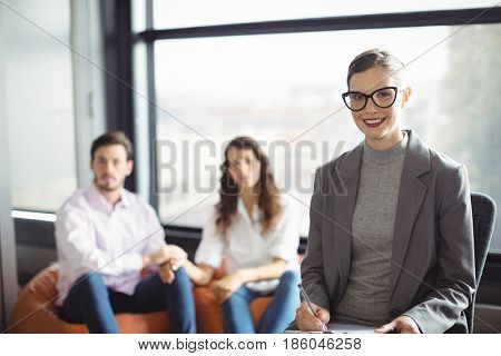 Portrait of smiling marriage counselor with couple in background
