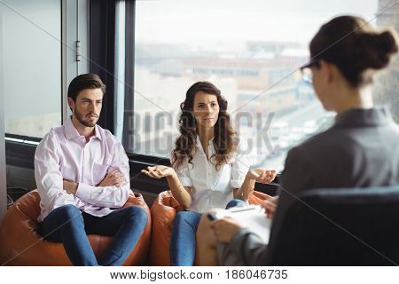 Annoyed couple talking to a marriage counselor during therapy