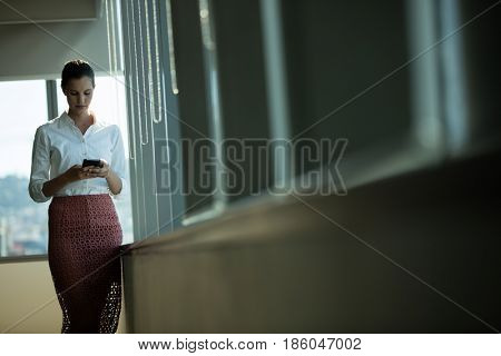 Well dressed businesswoman using mobile while standing by window in office