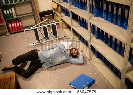 High angle view of fallen businessman and file in storage room at workplace