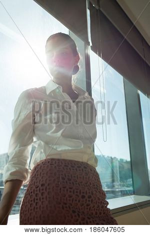 Low angle view of thoughtful businesswoman standing by brightly lit window in office